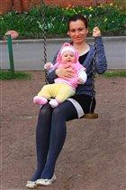 Мама с дочкой катаются на качелях