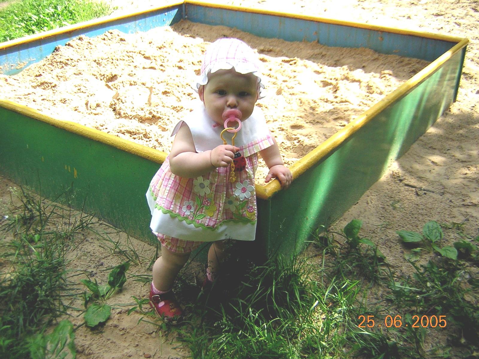 Кристинка возле песочницы. Я построил на песке...