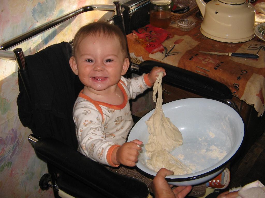 на даче,помогает месить тесто. Готовим вместе с мамой