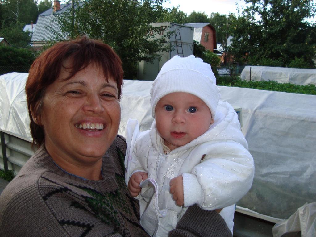 бабуля с внучиком отдыхают в саду. Стар и мал