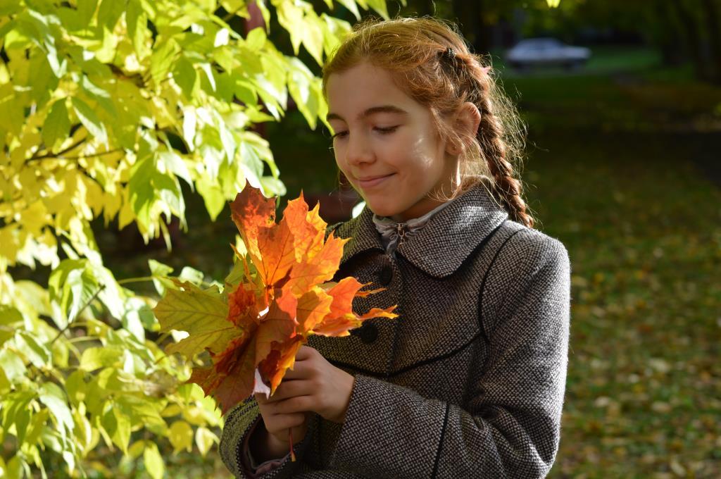 Доченька Арина с кленовыми листьями в руках. Краски осени