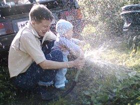 Папа и сын поливают огород