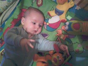 Пашенька  пытается дотянуться до своих любимых игрушек.