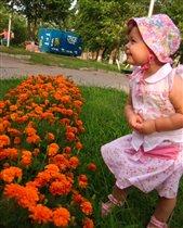 Лапочка-дочка, смотрит на цветочки