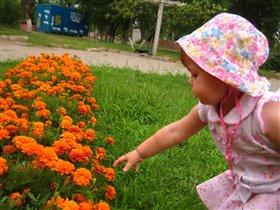 Лапочка-дочка смотрит на цветочки