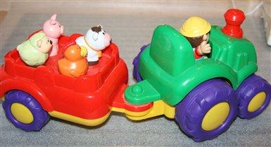 Разноцветный трактор с прицепом и веселыми животны