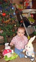 Серьезная Ариша под елкой внимательно наблюдает