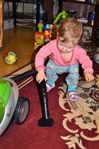 Милена помогает маме пылесосить ковер