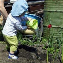 Садит с бабушкой цветы.