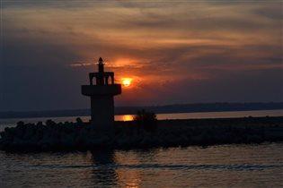 Закат собой окрасил море и даже тень от маяка
